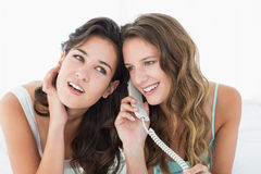 Jeunes amis féminins décontractés à l'aide du téléphone dans le lit Image stock