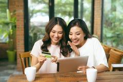 Jeunes amis féminins décontractés heureux faisant des achats en ligne  Photo libre de droits