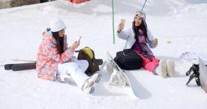 Jeunes amis féminins détendant avec des surfs des neiges Photo stock