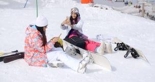 Jeunes amis féminins détendant avec des surfs des neiges Photos stock