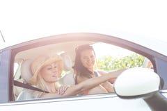Jeunes amis féminins dans la voiture le jour ensoleillé contre le ciel clair Photographie stock libre de droits
