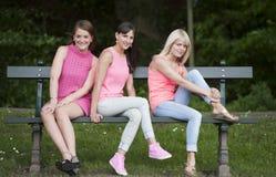 Jeunes amis féminins de Hree assis sur un banc, dehors Images stock