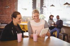 Jeunes amis féminins de sourire à l'aide de la tablette au café Photos stock