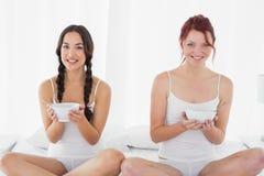 Jeunes amis féminins de sourire avec des cuvettes se reposant sur le lit Photographie stock libre de droits