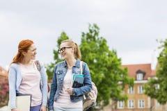 Jeunes amis féminins de sourire d'université marchant dehors Image stock