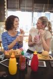 Jeunes amis féminins de sourire parlant au café Photos libres de droits