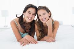 Jeunes amis féminins de sourire se situant dans le lit Image libre de droits
