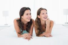 Jeunes amis féminins de sourire se situant dans le lit Photographie stock libre de droits