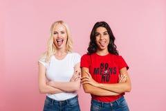 Jeunes amis féminins drôles montrant la langue d'isolement Photo libre de droits