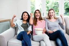Jeunes amis féminins encourageant tout en se reposant sur le sofa Photos libres de droits