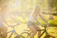 Jeunes amis féminins faisant un cycle au soleil Image stock