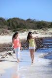 Jeunes amis féminins flânant à la plage Photographie stock