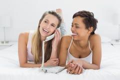 Jeunes amis féminins gais à l'aide du téléphone dans le lit Photos libres de droits
