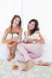 Jeunes amis féminins gais avec des tasses de café dans le lit Image libre de droits