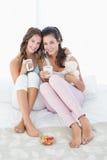 Jeunes amis féminins gais avec des tasses de café dans le lit Image stock