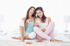 Jeunes amis féminins gais avec des tasses de café dans le lit Photo stock