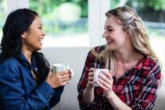 Jeunes amis féminins gais buvant du café à la maison Photographie stock libre de droits