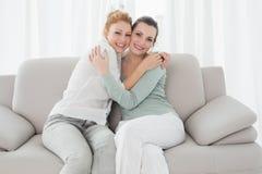 Jeunes amis féminins gais embrassant dans le salon Photo stock