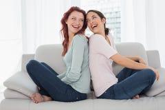 Jeunes amis féminins gais s'asseyant de nouveau au dos dans le salon Photos stock