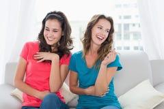Jeunes amis féminins gais s'asseyant sur le sofa à la maison Image libre de droits