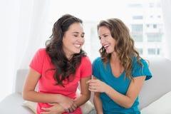Jeunes amis féminins gais s'asseyant sur le sofa à la maison Image stock