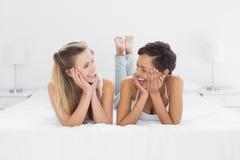 Jeunes amis féminins gais se situant dans le lit Image libre de droits