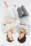 Jeunes amis féminins gais se situant dans le lit Photographie stock libre de droits