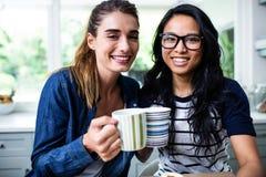 Jeunes amis féminins gais tenant la tasse de café Photo stock
