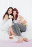 Jeunes amis féminins heureux avec des tasses de café dans le lit Image stock