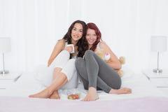 Jeunes amis féminins heureux avec des tasses de café dans le lit Image libre de droits