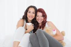 Jeunes amis féminins heureux avec des tasses de café dans le lit Photo stock
