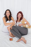 Jeunes amis féminins heureux avec des tasses de café dans le lit Photographie stock libre de droits