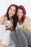 Jeunes amis féminins heureux avec des tasses de café dans le lit Photo libre de droits