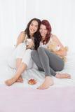 Jeunes amis féminins heureux avec des tasses de café dans le lit Images libres de droits
