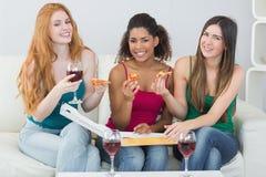 Jeunes amis féminins heureux avec la pizza et le vin à la maison Images stock