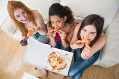 Jeunes amis féminins heureux avec la pizza et le vin sur le sofa Photo stock