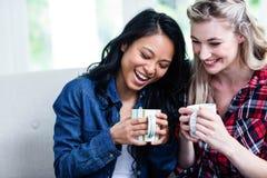 Jeunes amis féminins heureux buvant du café à la maison Images libres de droits