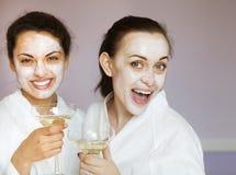 Jeunes amis féminins heureux buvant du champagne dans la station thermale image libre de droits