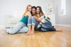 Jeunes amis féminins heureux embrassant sur le plancher à la maison Photographie stock libre de droits