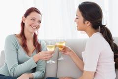 Jeunes amis féminins heureux grillant des verres de vin à la maison Image libre de droits