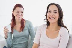 Jeunes amis féminins heureux s'asseyant à la maison Photos libres de droits