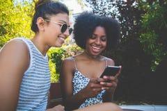 Jeunes amis féminins heureux s'asseyant dehors utilisant le mobile Photographie stock