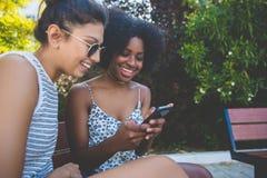 Jeunes amis féminins heureux s'asseyant sur le banc utilisant le mobile Images libres de droits