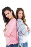 Jeunes amis féminins heureux se tenant de nouveau au dos Photo stock