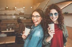Jeunes amis féminins joyeux amusant en café Images stock