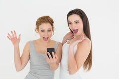 Jeunes amis féminins occasionnels choqués avec le téléphone portable Photographie stock libre de droits