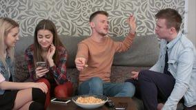 Jeunes amis féminins occasionnels heureux riant de ce qu'elles voient à un téléphone portable, alors que leurs amis masculins par Photos stock