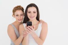 Jeunes amis féminins occasionnels regardant le téléphone portable Photos stock