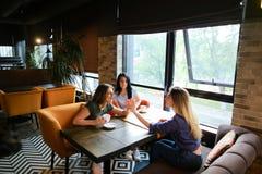 Jeunes amis féminins parlant au café et à l'aide du smartphone, café potable Photo libre de droits