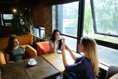 Jeunes amis féminins parlant au café et à l'aide du smartphone pour des photos, café potable Photographie stock